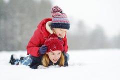 Dos niñas adorables que se divierten junto en parque hermoso del invierno Hermanas hermosas que juegan en una nieve imagenes de archivo