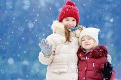 Dos niñas adorables que se divierten junto en parque hermoso del invierno Hermanas hermosas que juegan en una nieve imágenes de archivo libres de regalías