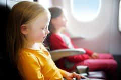 Dos niñas adorables que viajan por un aeroplano Niños que se sientan por la ventana de los aviones y que miran afuera Imagen de archivo libre de regalías
