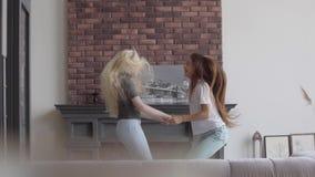 Dos niñas con el pelo rubio y oscuro que salta llevando a cabo las manos en la sala de estar Muchacha morena y muchacha del albin almacen de video