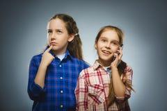 Dos niñas con el teléfono celular son reunión en línea sobre un fondo gris Fotografía de archivo