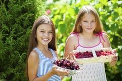 Dos niñas con las cerezas y las frambuesas Fotografía de archivo