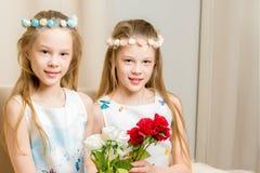 Dos niñas con las flores Fotos de archivo