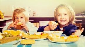 Dos niñas con los postres poner crema foto de archivo