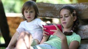 Dos niñas con smartphone rojo se sientan en banco del oscilación almacen de metraje de vídeo