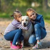 Dos niñas con un perro Amor fotografía de archivo libre de regalías