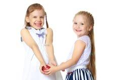 Dos niñas con una manzana Fotos de archivo