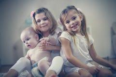 Dos niñas cuidan a un hermano del bebé fotos de archivo