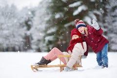 Dos niñas divertidas que se divierten con un juego en parque hermoso del invierno Niños lindos que juegan en una nieve fotos de archivo
