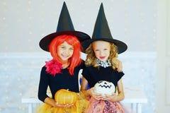 Dos niñas en el traje de la bruja que juega con las calabazas Fotos de archivo