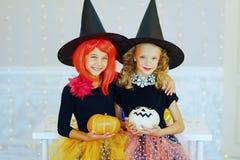 Dos niñas en el traje de la bruja que juega con las calabazas Imagen de archivo