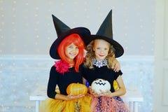 Dos niñas en el traje de la bruja que juega con las calabazas Imagen de archivo libre de regalías