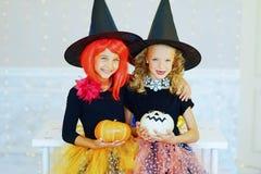 Dos niñas en el traje de la bruja que juega con las calabazas Foto de archivo