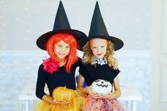 Dos niñas en el traje de la bruja que juega con las calabazas Imagenes de archivo