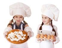 Dos niñas en un delantal blanco que sostiene la caja de huevos crudos y de pi Foto de archivo libre de regalías