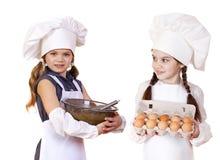 Dos niñas en un delantal blanco que sostiene la caja de huevos y de BO crudos Fotografía de archivo