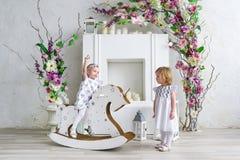 Dos niñas encantadoras juegan en el cuarto ligero adornado con las flores Bebé que balancea en un caballo de madera Imágenes de archivo libres de regalías