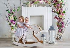 Dos niñas encantadoras juegan en el cuarto ligero adornado con las flores Bebés que balancean en un caballo de madera Imagenes de archivo
