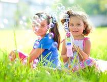 Dos niñas están soplando burbujas de jabón fotos de archivo