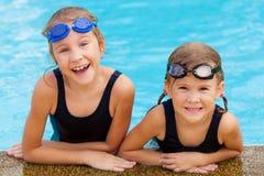 Dos niñas felices en la piscina Imágenes de archivo libres de regalías