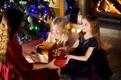 Dos niñas felices que consiguen un regalo de la Navidad de su mamá Fotos de archivo