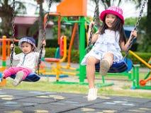 Dos niñas felices que juegan el oscilación en el patio Feliz, F imagen de archivo libre de regalías