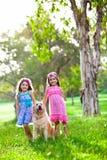 Dos niñas felices y un perro perdiguero de oro imagen de archivo