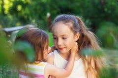 Dos niñas lindas que abrazan y que juegan en el parque en el día Foto de archivo