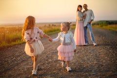 Dos niñas miran uno a, el paseo abajo del camino y llevan a cabo las manos al aire libre en la puesta del sol foto de archivo
