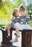Dos niñas o hermanas rubias felices que se sientan en un banco y que miran la tableta Imágenes de archivo libres de regalías