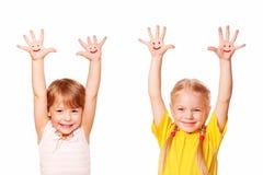 Dos niñas que aumentan sus manos para arriba. Estudiantes jovenes Foto de archivo libre de regalías