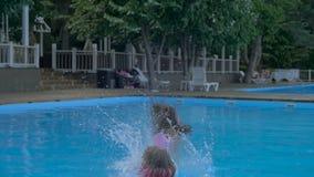Dos niñas que caen en piscina en el aquapark Silla de cubierta en la playa en Brighton metrajes