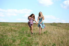 Dos niñas que corren en campo del verano Imagen de archivo libre de regalías
