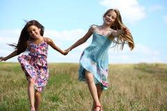 Dos niñas que corren en campo del verano Fotos de archivo