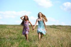 Dos niñas que corren en campo del verano Imágenes de archivo libres de regalías