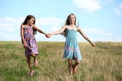 Dos niñas que corren en campo del verano Fotografía de archivo libre de regalías