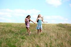 Dos niñas que corren en campo del verano Foto de archivo