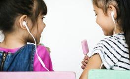 Dos niñas que escuchan la música imágenes de archivo libres de regalías