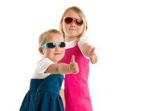 Dos niñas que muestran los pulgares para arriba Foto de archivo