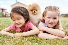 Dos niñas que presentan con el perrito al aire libre Fotos de archivo libres de regalías