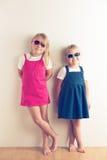 Dos niñas que presentan delante de una pared fotografía de archivo