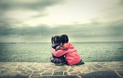 Dos niñas que se sientan cerca del mar imagenes de archivo