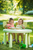 Dos niñas que se sientan en una tabla y que comen junto contra césped verde Fotos de archivo libres de regalías
