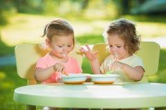 Dos niñas que se sientan en una tabla y que comen junto contra césped verde Foto de archivo libre de regalías
