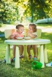Dos niñas que se sientan en una tabla y que comen junto contra césped verde Imagenes de archivo