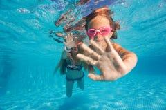 Dos niñas que se zambullen bajo el agua en piscina Fotos de archivo libres de regalías