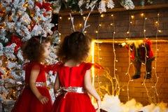 Dos niñas rizadas que miran la chimenea de la Navidad cerca de b fotos de archivo libres de regalías