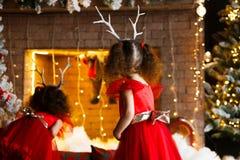 Dos niñas rizadas que miran la chimenea de la Navidad cerca de b imagenes de archivo
