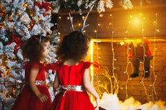 Dos niñas rizadas que miran la chimenea de la Navidad cerca de b fotos de archivo