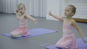Dos niñas se sientan en sus revestimientos y bailan ejercicios en el entrenamiento almacen de video